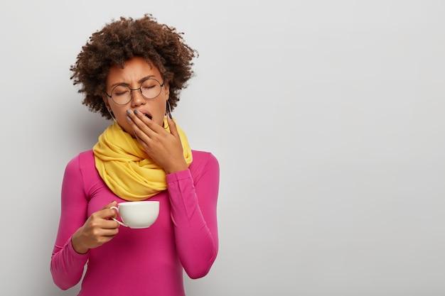 Mulher cacheada cansada bocejando, tem uma expressão sonolenta, bebe café de manhã cedo, segura uma caneca branca de bebida quente