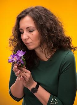 Mulher cacheada cheirando flores de açafrão com olhos fechados em um fundo amarelo