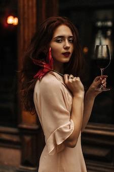 Mulher cacheada em um vestido bege segurando flores e vinho