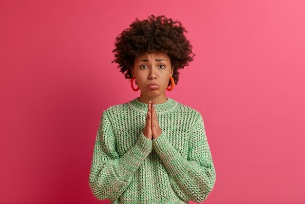 Mulher cacheada soluçando descontente olha com expressão sombria, dá as mãos para rezar, pede desculpas, ajuda ou favor, precisa muito de algo, vestida de suéter de tricô, presa em situação difícil