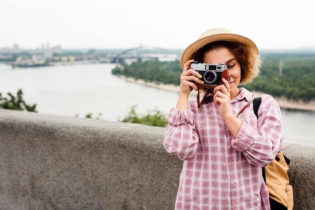 Mulher cacheada tirando uma foto com espaço de cópia