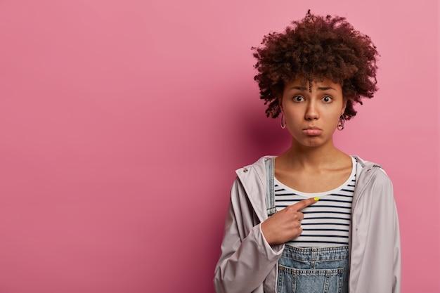 Mulher cacheada triste decepcionada sendo selecionada, não entende porque é que é culpada, aponta para si mesma, franze o lábio inferior e quer chorar de desespero, usa blusa listrada e anoraque, pergunta por que eu