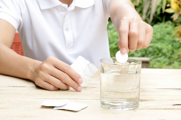Mulher caindo tablet efervescente em copo de água na mesa de madeira