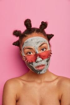 Mulher calma com aparência séria usa máscara de beleza, fica sem camisa dentro de casa, usa óculos escuros rosados, reduz rugas e cravos, isolados na parede rosa. tiro vertical. rejuvenescimento, bem-estar