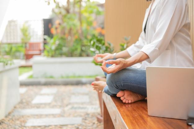 Mulher calma com olhos fechados praticando ioga em posição de lótus