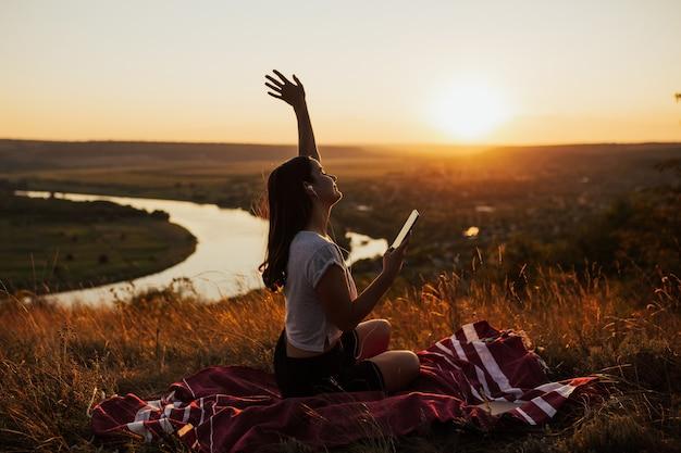 Mulher calma e relaxada está sentada na colina com bela paisagem no fundo.