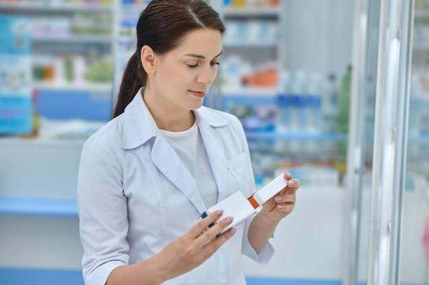 Mulher calma e sorridente a olhar para duas embalagens de medicamentos