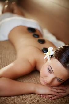 Mulher calma que aprecia o tratamento de pedra quente