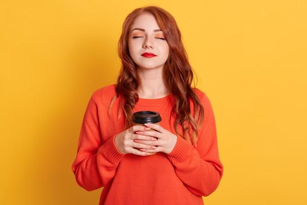 Mulher calma vestindo um suéter casual grande, segurando café para viagem com as duas mãos, desfrutando de uma bebida quente com os olhos fechados