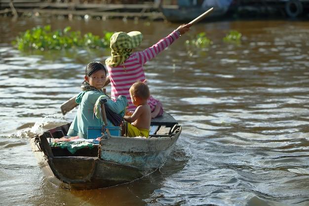 Mulher cambojana e duas crianças na aldeia inundada em siem reap, camboja