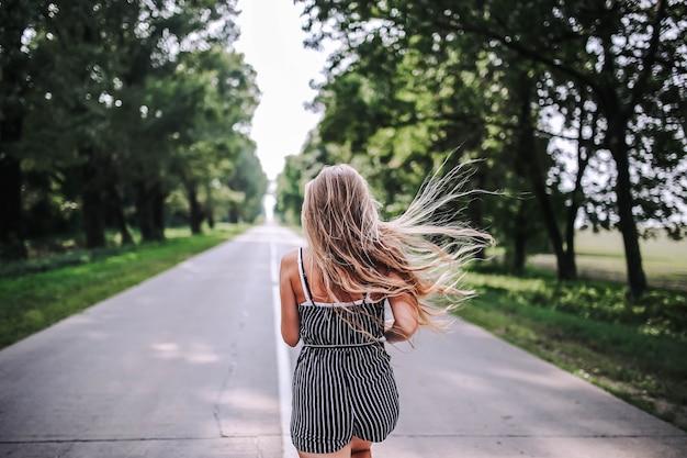 Mulher caminha ao longo da estrada entre a floresta nova vida no verão o conceito de um brilhante