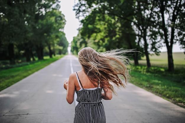 Mulher caminha ao longo da estrada entre a floresta para encontrar uma nova vida no verão o conceito de um brilhante