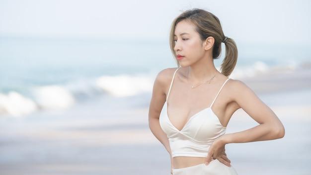 Mulher caminha ao longo da praia com o mar.