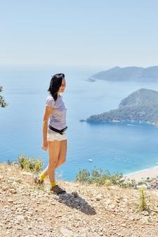 Mulher caminha ao longo da trilha da via lícia. fethiye, oludeniz. linda vista para o mar e para a praia