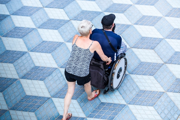 Mulher caminha com um homem com deficiência em cadeira de rodas, passeio descontraído ao pôr do sol