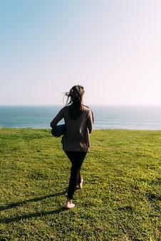 Mulher caminha de costas com uma esteira na grama para fazer ioga em frente ao mar. copie o espaço