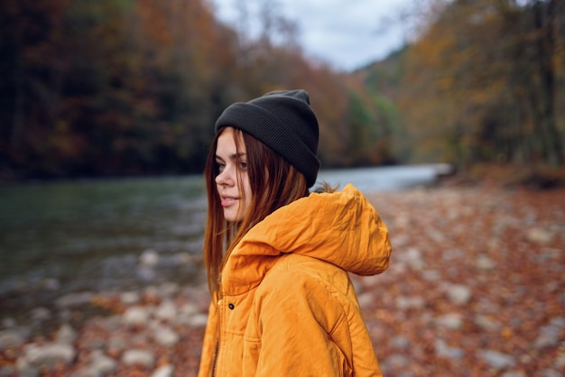 Mulher caminha na floresta de outono com uma jaqueta amarela.