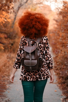 Mulher caminha no parque no outono