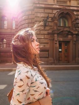 Mulher caminha pelas ruas, com edifício histórico de petersburgo