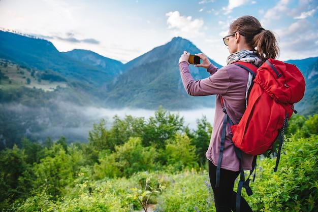 Mulher, caminhadas na montanha e tirar fotos com o telefone inteligente