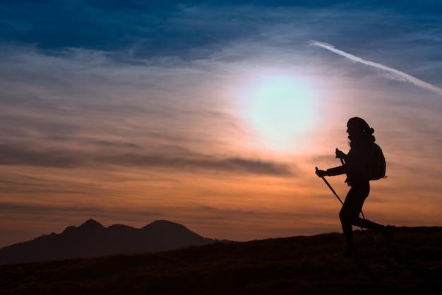 Mulher, caminhadas nas montanhas ao pôr do sol