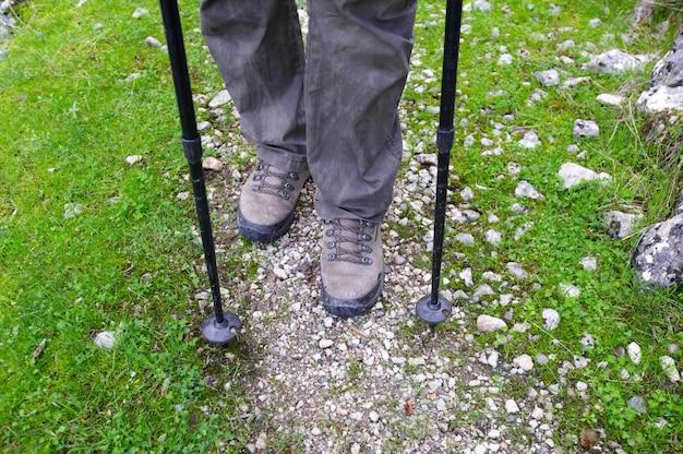 Mulher, caminhadas nas montanhas, aventura e exercício. pernas e bastões de caminhada nórdicos