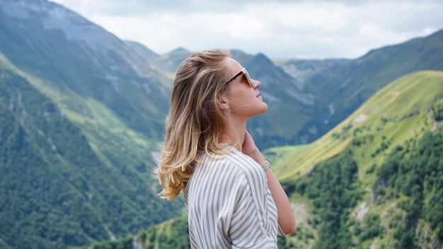 Mulher, caminhadas nas montanhas na hora do dia ensolarado. vista de kazbegi, geórgia