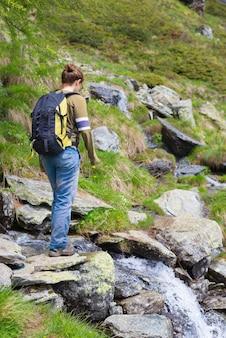 Mulher, caminhadas nos alpes, atravessando o pequeno riacho