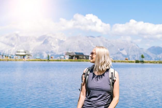 Mulher, caminhadas num lindo dia de verão nas montanhas dos alpes, áustria, descansando na rocha e admirar a vista incrível para os picos das montanhas.