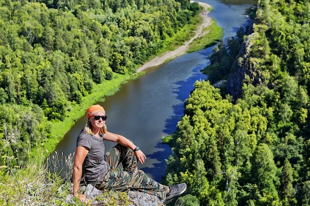 Mulher, caminhadas turísticas em bandana e óculos de sol, descansando no topo da montanha num dia ensolarado de verão.