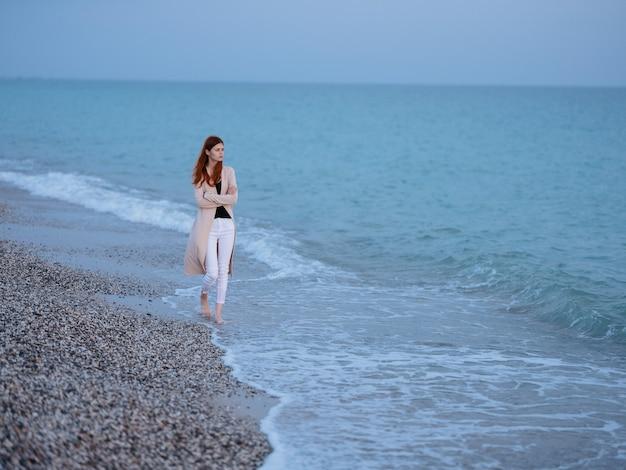 Mulher caminhando à beira-mar em repouso, liberdade, romance