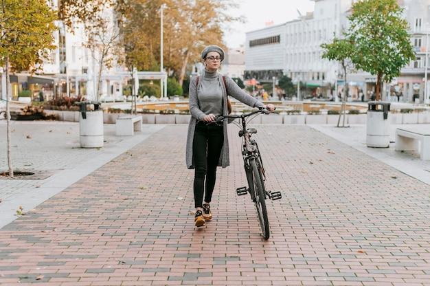 Mulher caminhando ao lado de sua bicicleta