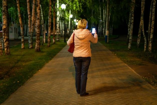 Mulher caminhando ao longo da calçada de um parque à noite