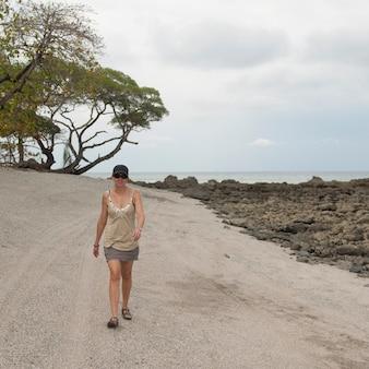 Mulher caminhando ao longo da estrada costeira na costa rica