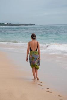 Mulher caminhando ao longo da praia em bali