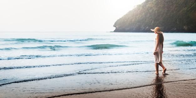 Mulher caminhando ao longo da praia