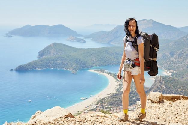 Mulher caminhando caminho da lícia com mochila. fethiye, oludeniz. linda vista para o mar e para a praia