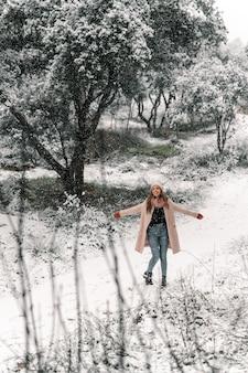 Mulher caminhando com os braços estendidos ao longo do caminho de neve e curtindo um passeio na floresta no inverno