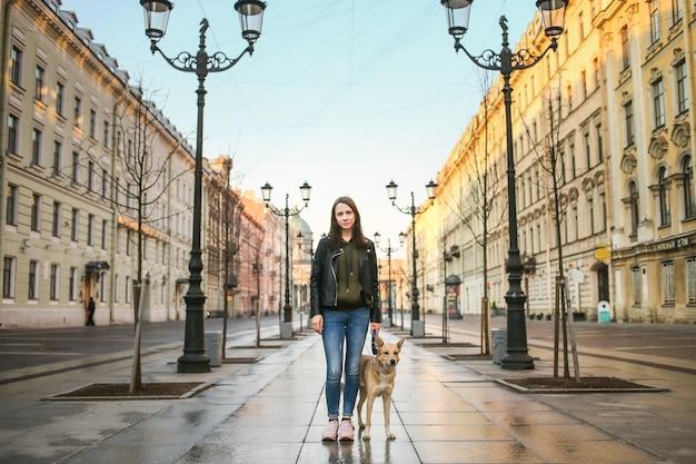 Mulher caminhando com um cachorro ao longo da rua contra a fachada de edifícios antigos no centro da cidade