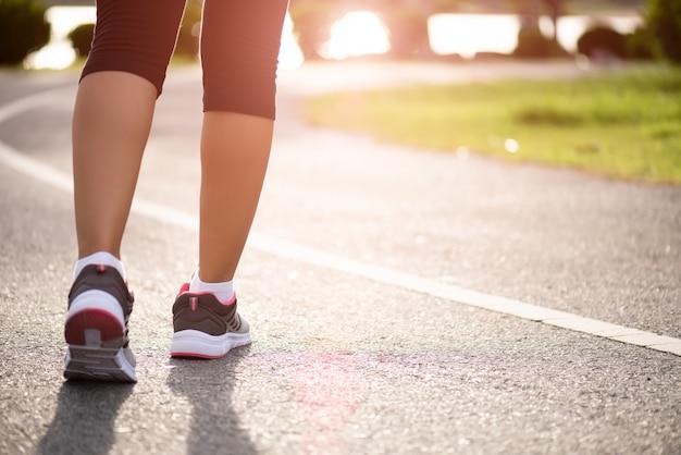 Mulher caminhando em direção ao lado da estrada. passo, caminhar e conceito de exercício ao ar livre.