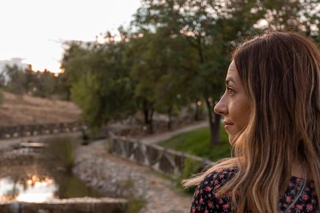 Mulher caminhando em um parque com água em um pôr do sol de outono. foco seletivo.
