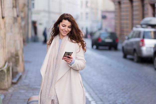 Mulher caminhando em uma nova cidade com um telefone nas mãos e uma mala