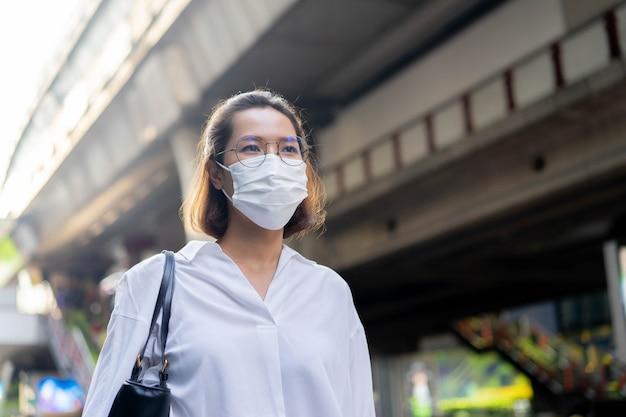 Mulher caminhando enquanto usa máscara facial para proteger o coronavírus e o crepúsculo da poluição