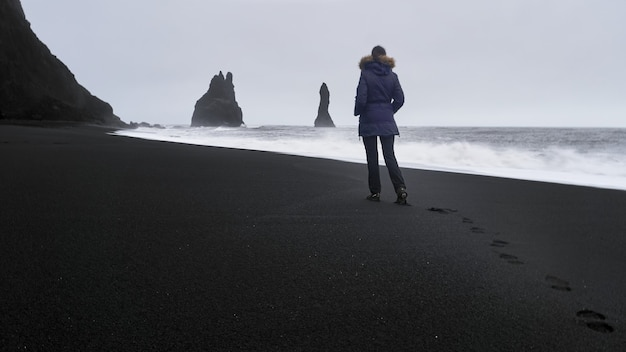 Mulher caminhando na costa de reynisfjara
