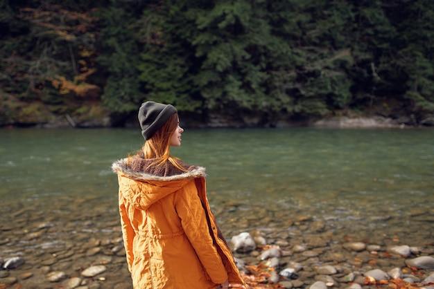 Mulher caminhando na floresta de outono perto do rio viaja