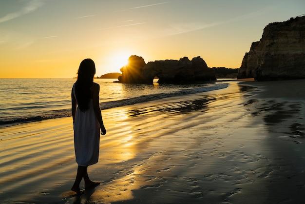Mulher caminhando na praia costeira no algarve, portugal
