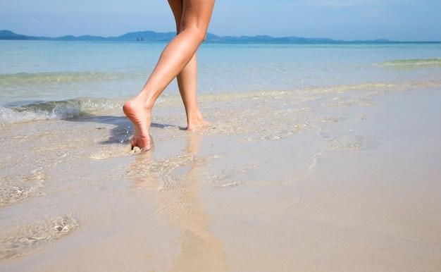 Mulher caminhando na praia de areia deixando pegadas na areia