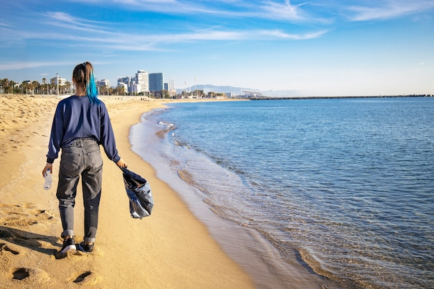 Mulher caminhando na praia e recolhendo lixo e garrafas plásticas, limpando a praia com um saco de lixo preto