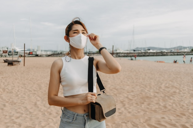 Mulher caminhando na praia no conceito de verão de férias de verão