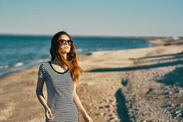 Mulher caminhando na praia perto do mar nas montanhas no verão na natureza